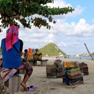 Women selling sarongs on Kuta beach.